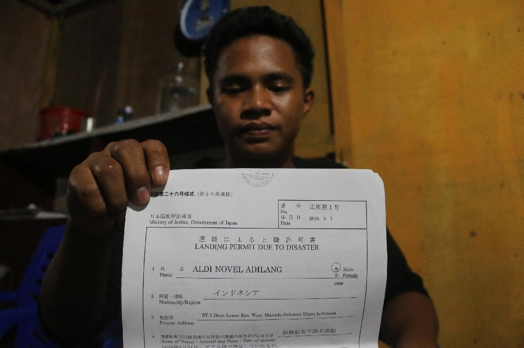 This picture taken in Wori, North Minahasa, Sulawesi on September 16, 2018 shows Indonesian teenager Aldi Novel Adilang holding a letter of landing permit due to disaster in Wori (AFP Photo/)