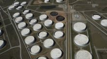 Oil plunge sets off search for storage tanks on land and sea