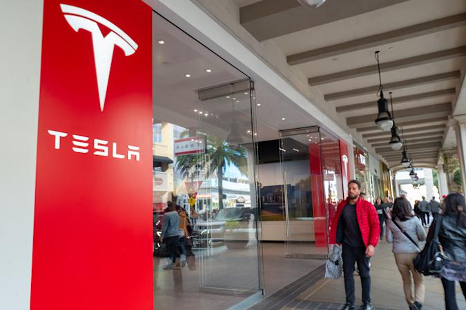 People walk past facade with logo at Tesla Motors store on Santana Row in the Silicon Valley, San Jose, California, December 14, 2019. (Photo by Smith Collection/Gado/Getty Images)
