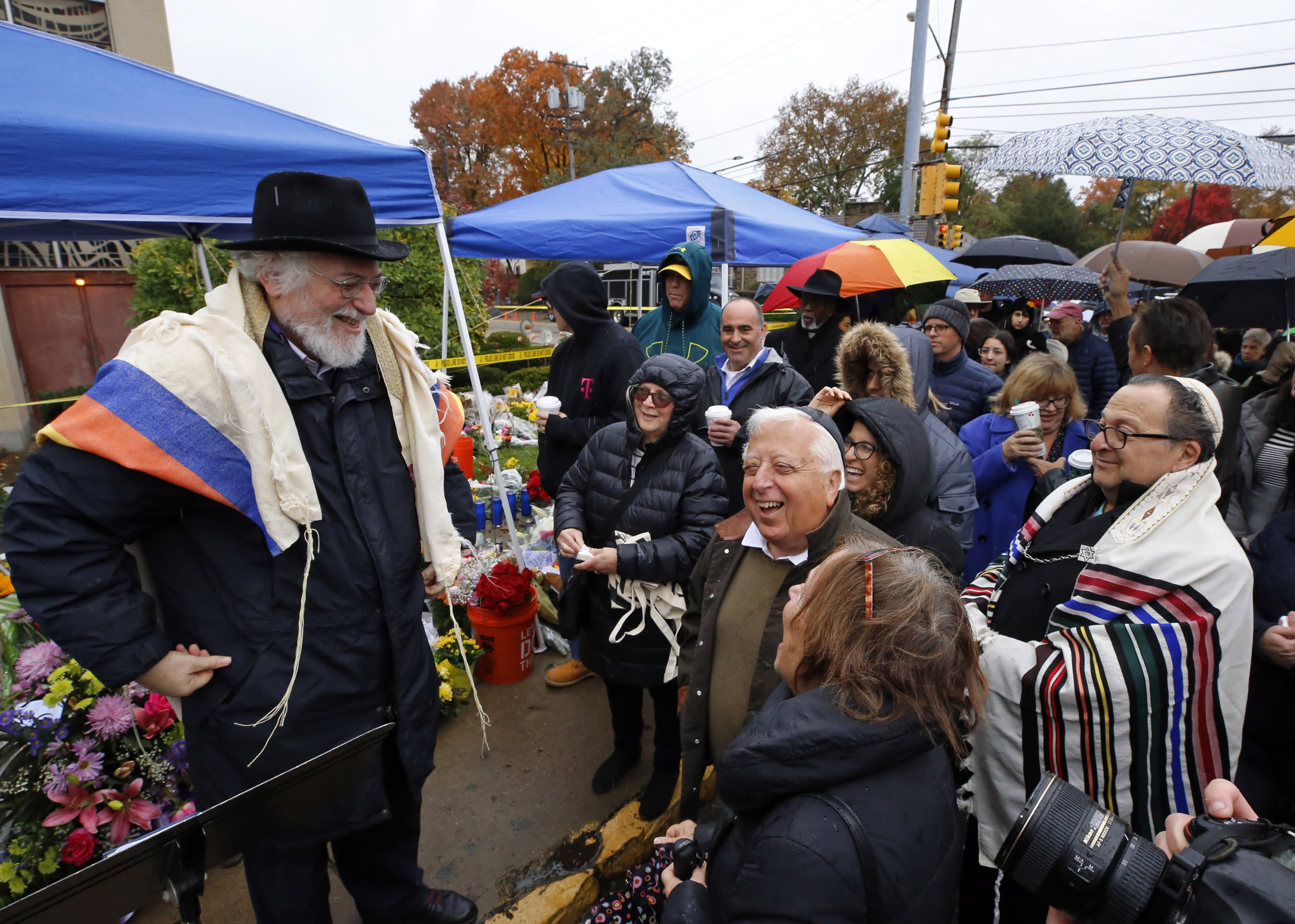 """Rabbi Chuck Diamond, left, a former Rabbi at the Tree of Life Synagogue, shares a laugh with worshipers before leading a Shabbat service outside the Tree of Life Synagogue, Saturday, Nov. 3, 2018 in Pittsburgh. About 100 people gathered in a cold drizzle for what was called a """"healing service"""" outside the synagogue that was the scene of a mass shooting a week ago. (AP Photo/Gene J. Puskar)"""