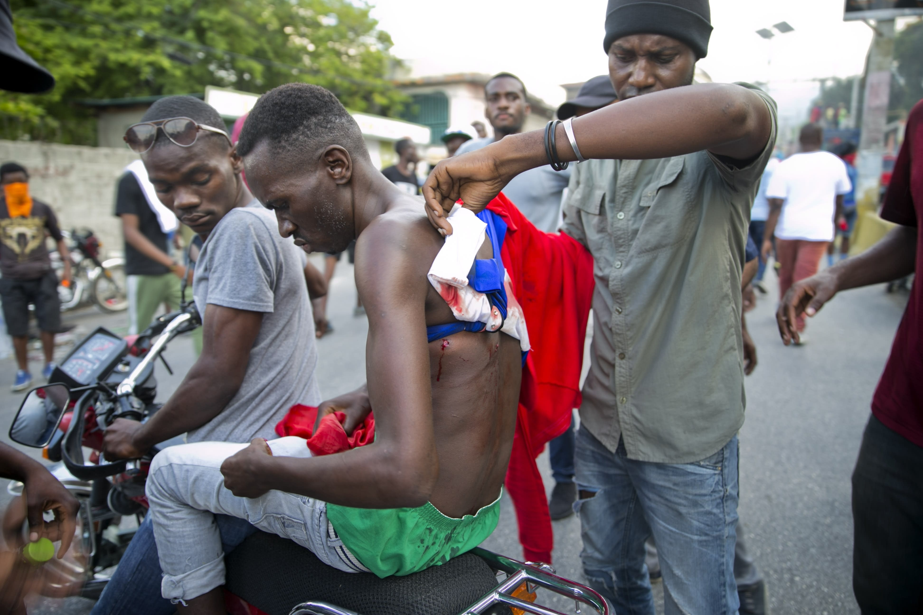 A wounded man is evacuated on a motorcycle during clashes to demand the resignation of Haiti's president Jovenel Moise on the 216th anniversary of Battle of Vertieres in Port-au-Prince, Haiti, Monday, Nov. 18, 2019. At least four people were shot and wounded during a small protest in Haiti's capital after a speech by embattled President Jovenel Moise. A local journalist, a police officer and two protesters were rushed away with apparent bullet wounds. (AP Photo/Dieu Nalio Chery)