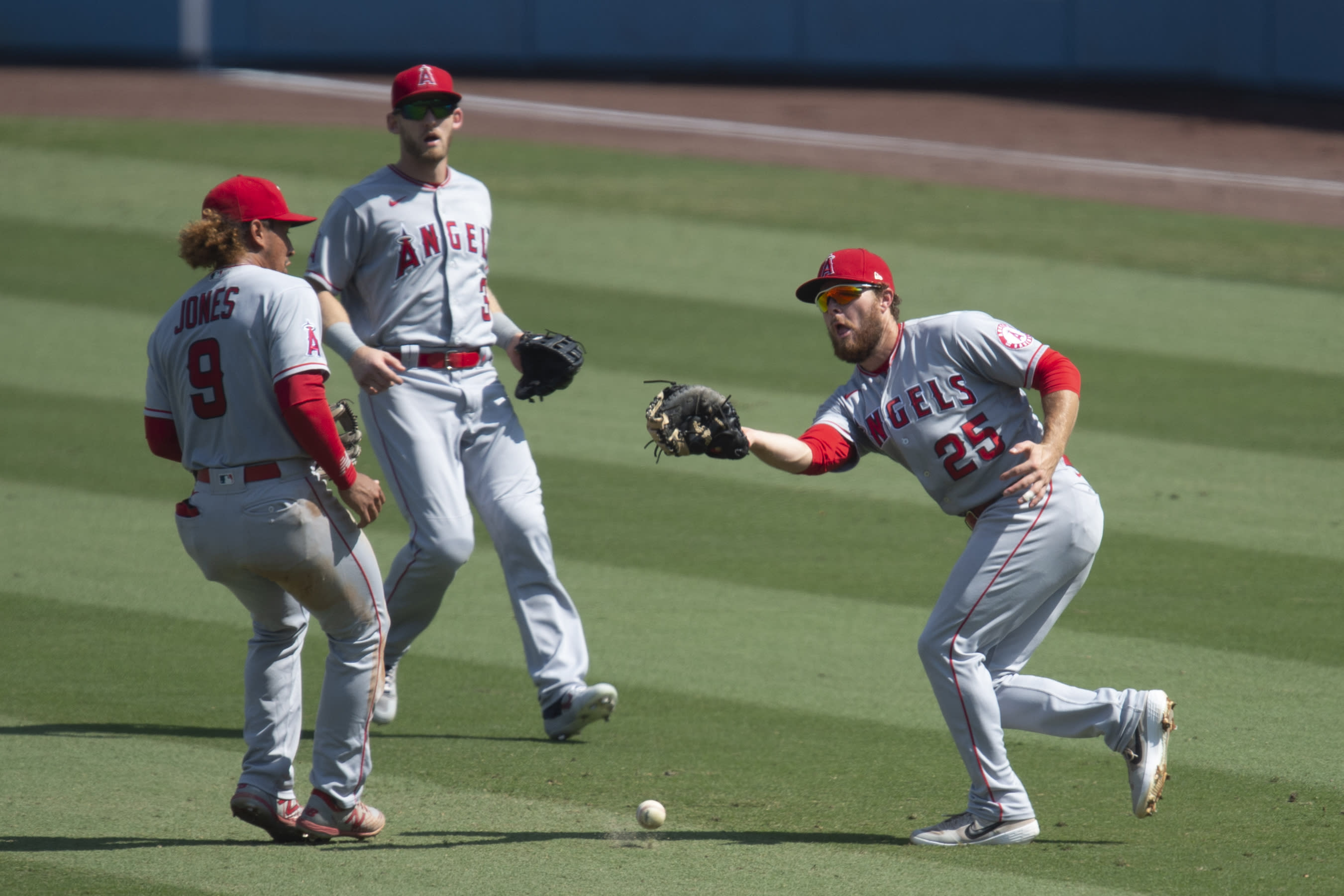 Los Angeles Angels first baseman Jared Walsh, right, cannot catch a fly ball off the bat of Los Angeles Dodgers' Justin Turner during the third inning of a baseball game in Los Angeles, Sunday, Sept. 27, 2020. (AP Photo/Kyusung Gong)