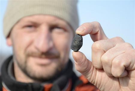 A local resident shows a fragment thought to be part of a meteorite collected in a snow covered field in the Yetkulski region outside the Urals city of Chelyabinsk