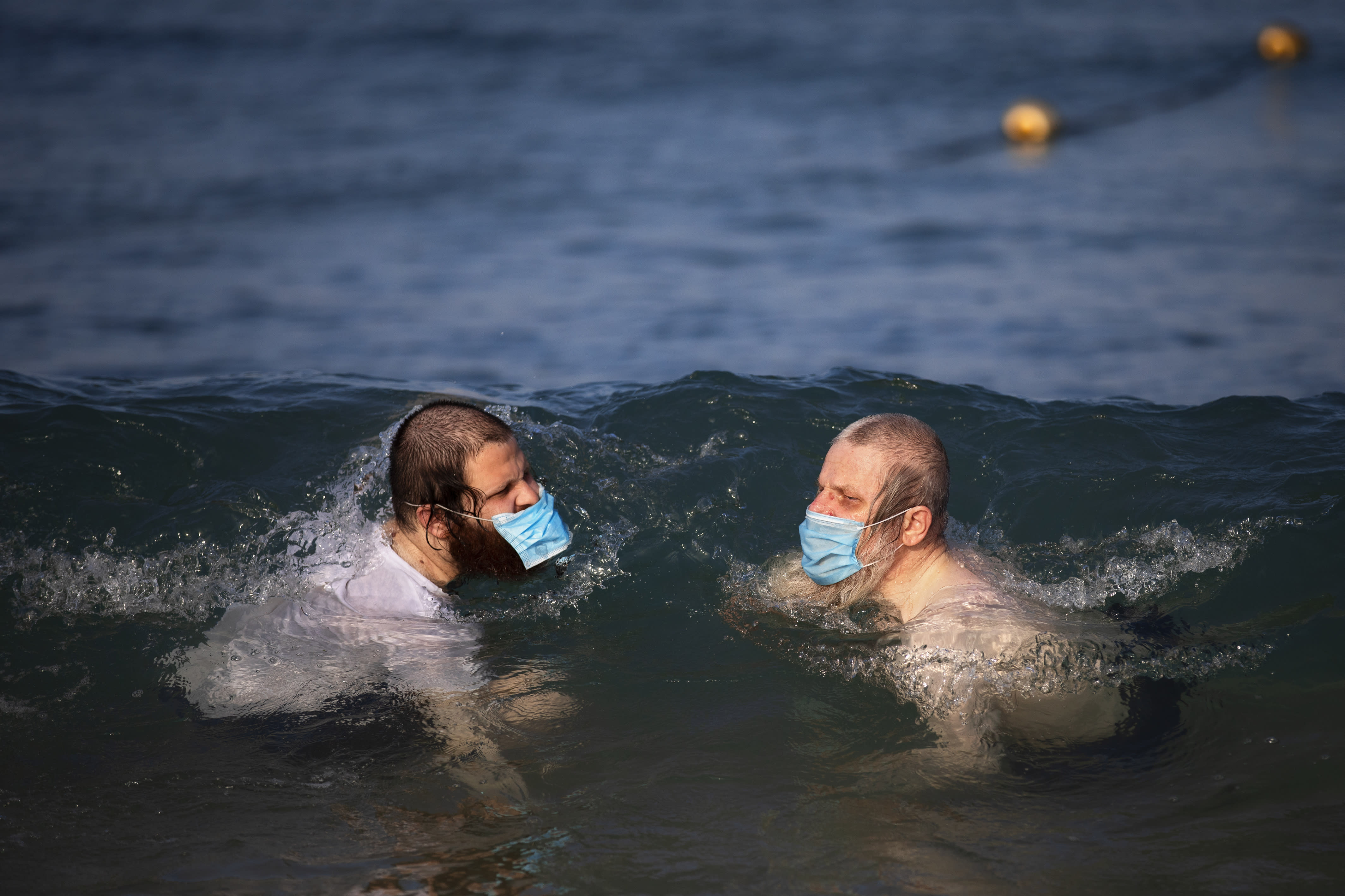 Ultra-orthodox Jewish men wearing protective face masks swim in the Mediterranean Sea, on a beach segregated for males three days a week, in Tel Aviv, Israel, Wednesday, July 8, 2020. In an effort to quell the rapid spread of the coronavirus, Israel has re-imposed a series of restrictions on the public. This week, the Israeli government limited gatherings and ordered reception halls, restaurants, bars, theaters, fitness centers and pools be shut down again. (AP Photo/Oded Balilty)