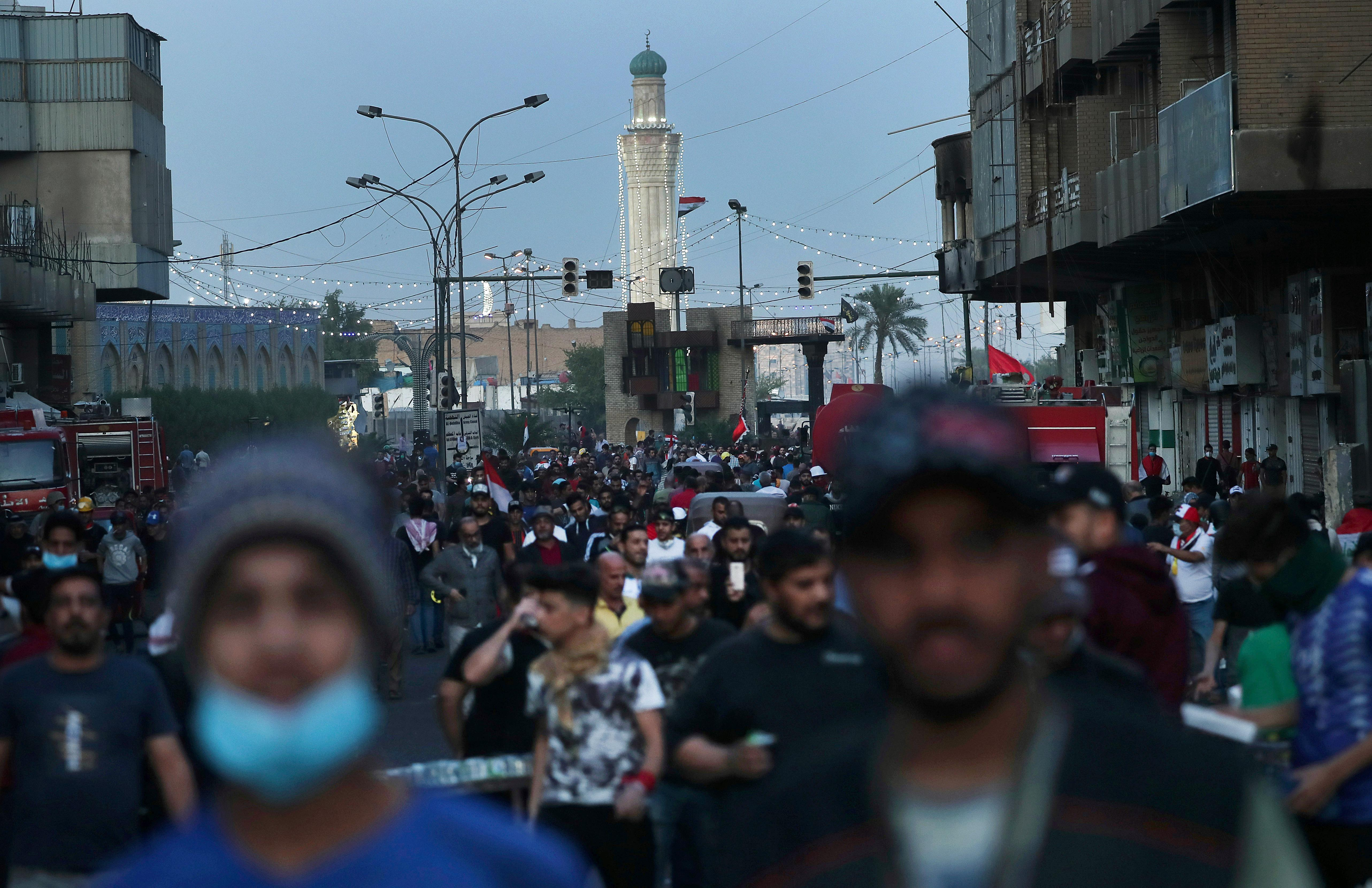 People walk through Khilani Square after protesters took control and reopened it, after clashes between Iraqi security forces and anti-government demonstrators in Baghdad, Iraq, Saturday, Nov. 16, 2019. (AP Photo/Hadi Mizban)