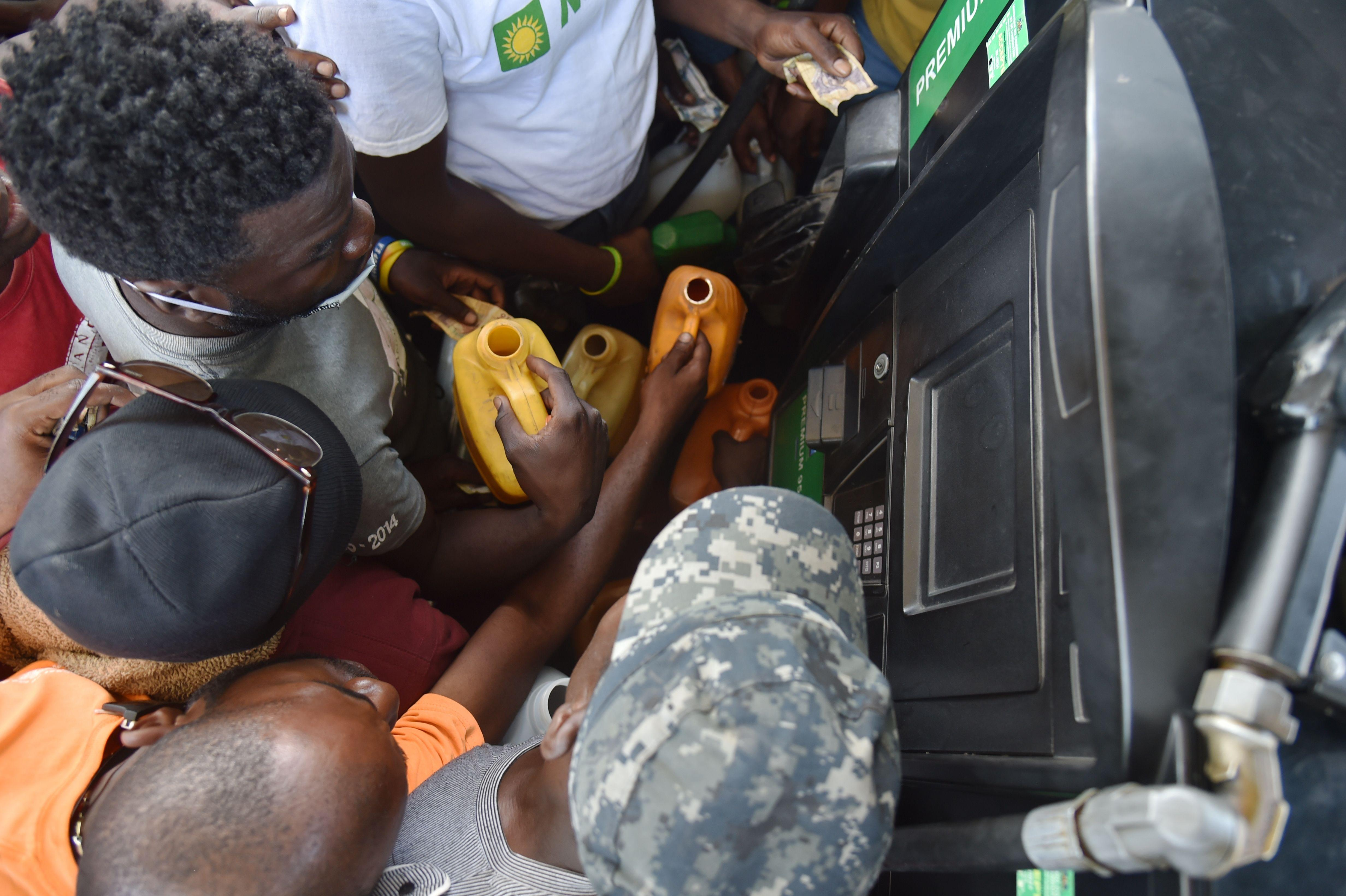 <p>Haitian people wait to purchase fuel at a gas station in the commune of Petion Ville in the Haitian capital Port-au-Prince, July 9, 2018, one of the few gas stations open during the strike to protest the hike in fuel prices. (Photo: Hector Retamal/AFP/Getty Images) </p>
