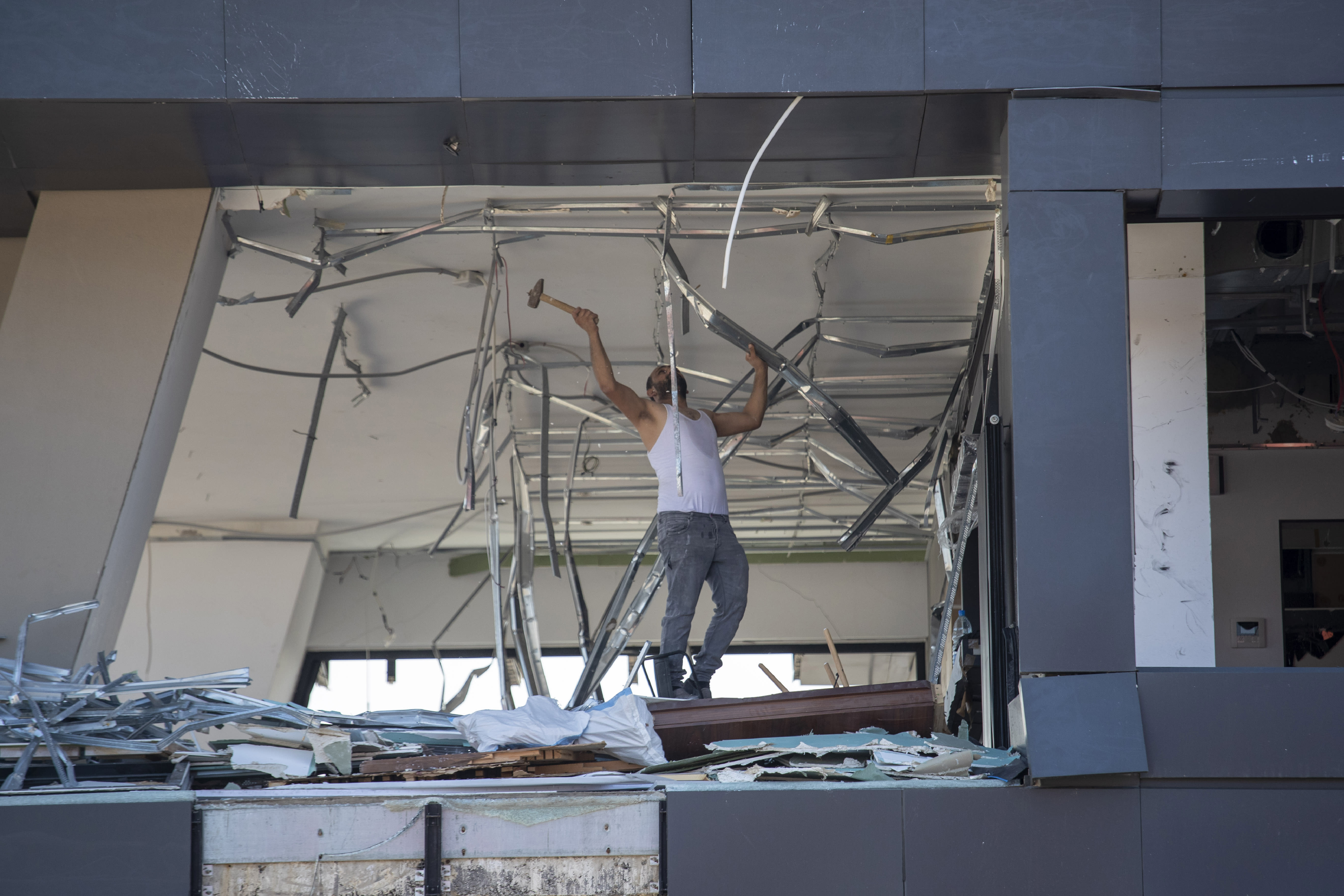 A man removes debris from a damaged building near the site of the Aug. 4 explosion that killed more than 170 people, injured thousands and caused widespread destruction, in Beirut, Lebanon, Friday, Aug. 14, 2020. (AP Photo/Hassan Ammar)