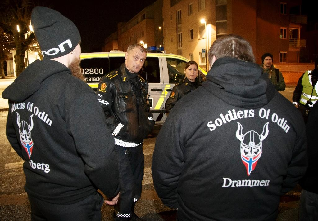 """Police officers control members of the so-called """"Soldiers of Odin"""" volunteer street patrol as they patrol through the streets of Drammen, Norway, on February 21, 2016"""