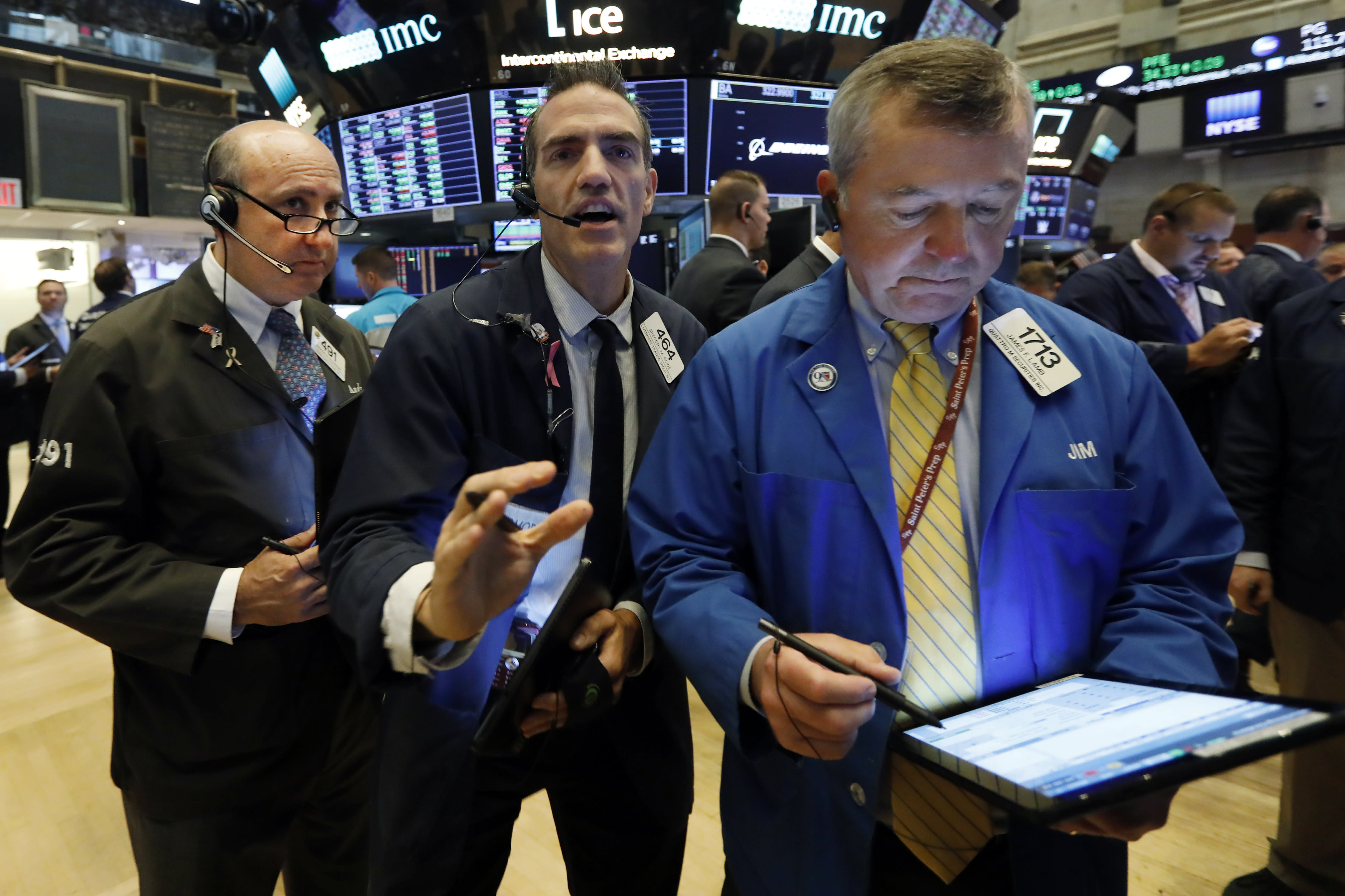 Traders Andrew Silverman, Gregory Rowe, and James Lamb, left to right work on the floor of the New York Stock Exchange, Thursday, Aug. 15, 2019. Stocks are rising on Wall Street early Thursday on indications American consumers continue to spend and embrace online shopping. (AP Photo/Richard Drew)