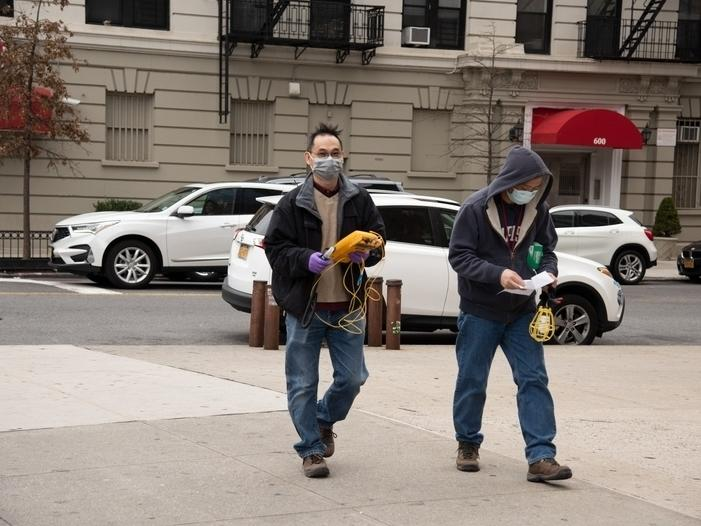 Two men with masks walking in the Washington Heights neighborhood of Manhattan.