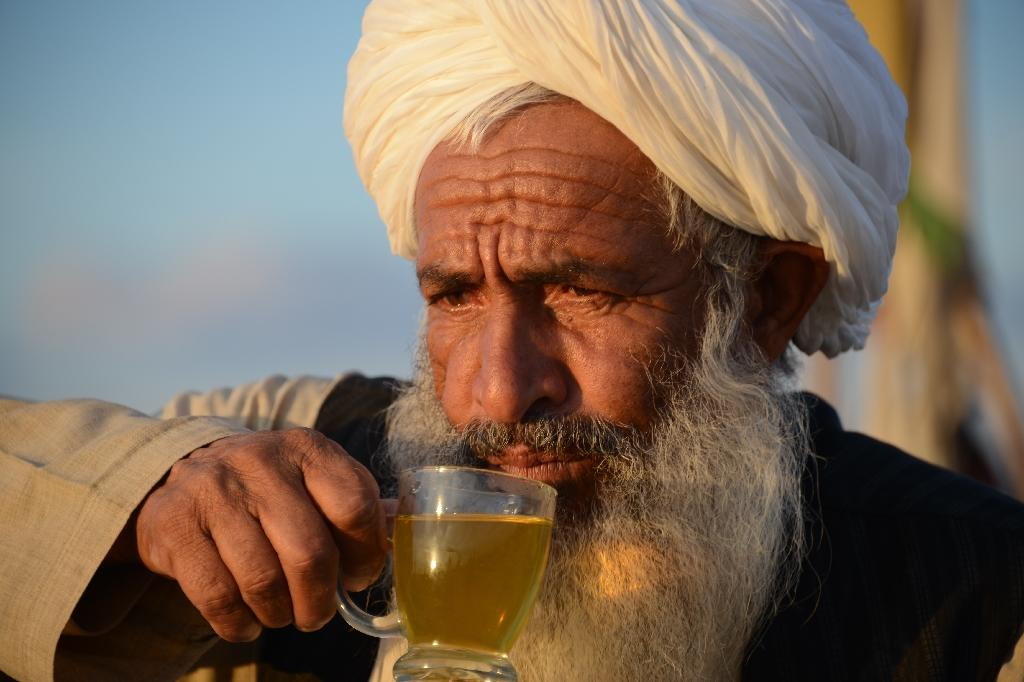 """Undertaker Malik Abdul Hakim during a tea break at a cemetery known as the """"Taliban graveyard"""" in the Zherai district of Kandahar (AFP Photo/Jawed Tanveer)"""
