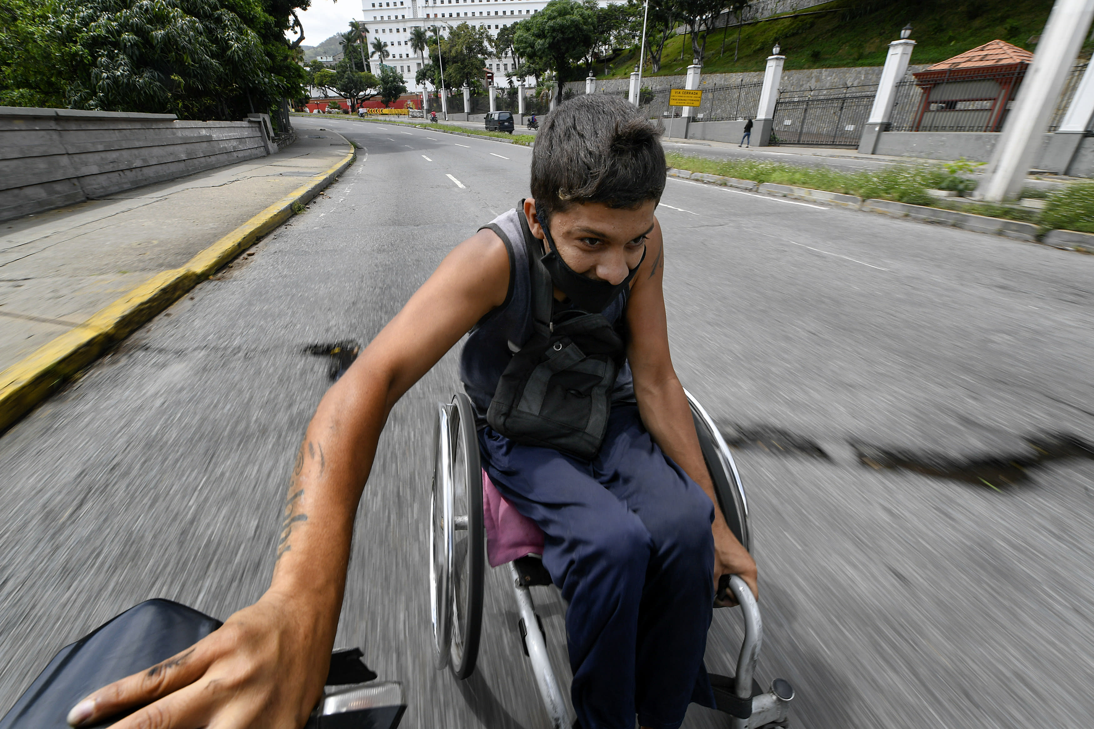 A man wearing a protective face mask hitches a ride in his wheelchair by grabbing on to the back of a motorcycle near the Miraflores Palace in Caracas Venezuela Saturday Aug. 8 2020 amid the new coronavirus pandemic