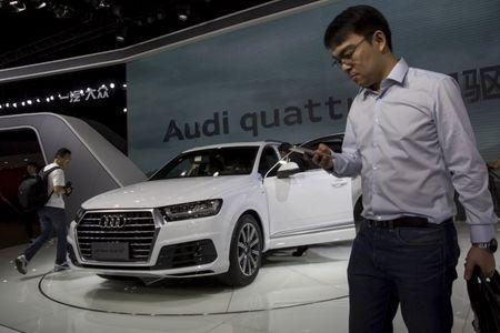 People walk past a Audi new Q7 car at the 13th China (Guangzhou) International Automobile Exhibition in Guangzhou, China