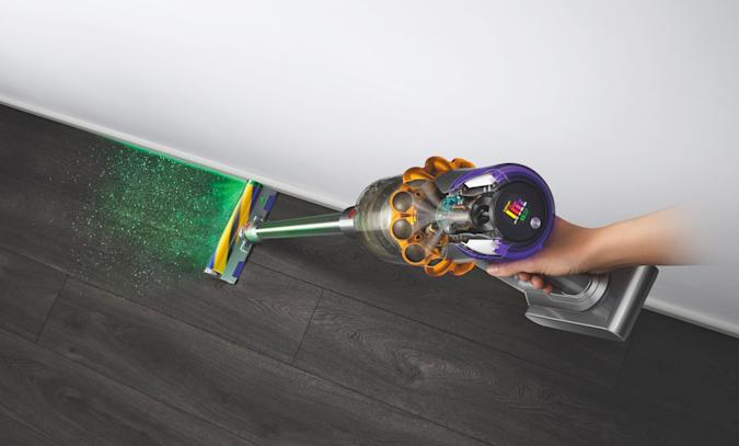 An artists rendering of the Dyson v15 Detect (with laser sighting) in action, being held by a disembodied hand.