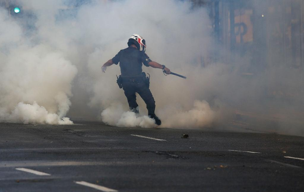 A policeman kicks a tear gas canister as supporters of suspended Brazilian president Dilma Rousseff protest against interim President Michel Temer in Sao Paulo on June 1, 2016 (AFP Photo/Miguel Schincariol)