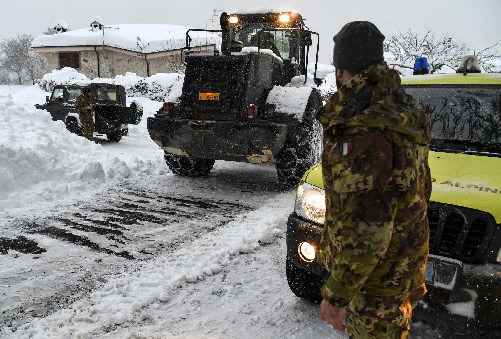 An Italian soldier takes part in an operation to clear snow from a street in Arigno, near Montereale, after fresh earthquakes on January 18, 2017 (AFP Photo/ANDREAS SOLARO)