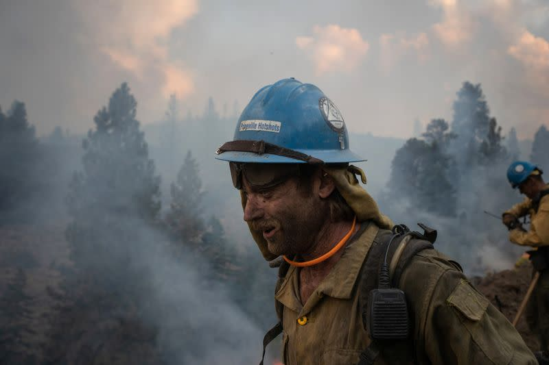 Firefighter walks past smoke rising from Brattain Fire in Fremont National Forest in Paisley, Oregon