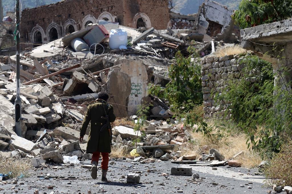 A Yemeni man inspects the damage on a street following clashes on November 22, 2016 in Taez (AFP Photo/AHMAD AL-BASHA)