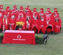 Very good boy crashes high school graduation, 'waters' the plants in the middle of class photo