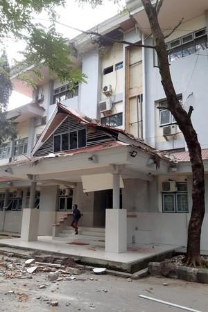 A resident walks through a damaged university building following an earthquake in Ambon
