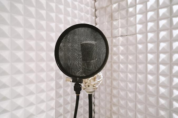 microphone with pop filter on mic stand in soundproof isolation booth for vocal recording at sound studio