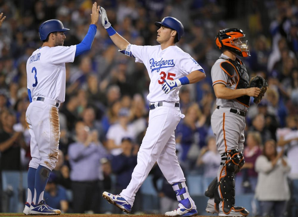 Dodgers' rookie Cody Bellinger congratulated by Chris Taylor after hitting a three-run home run in the Dodgers division-clinching win. (AP)