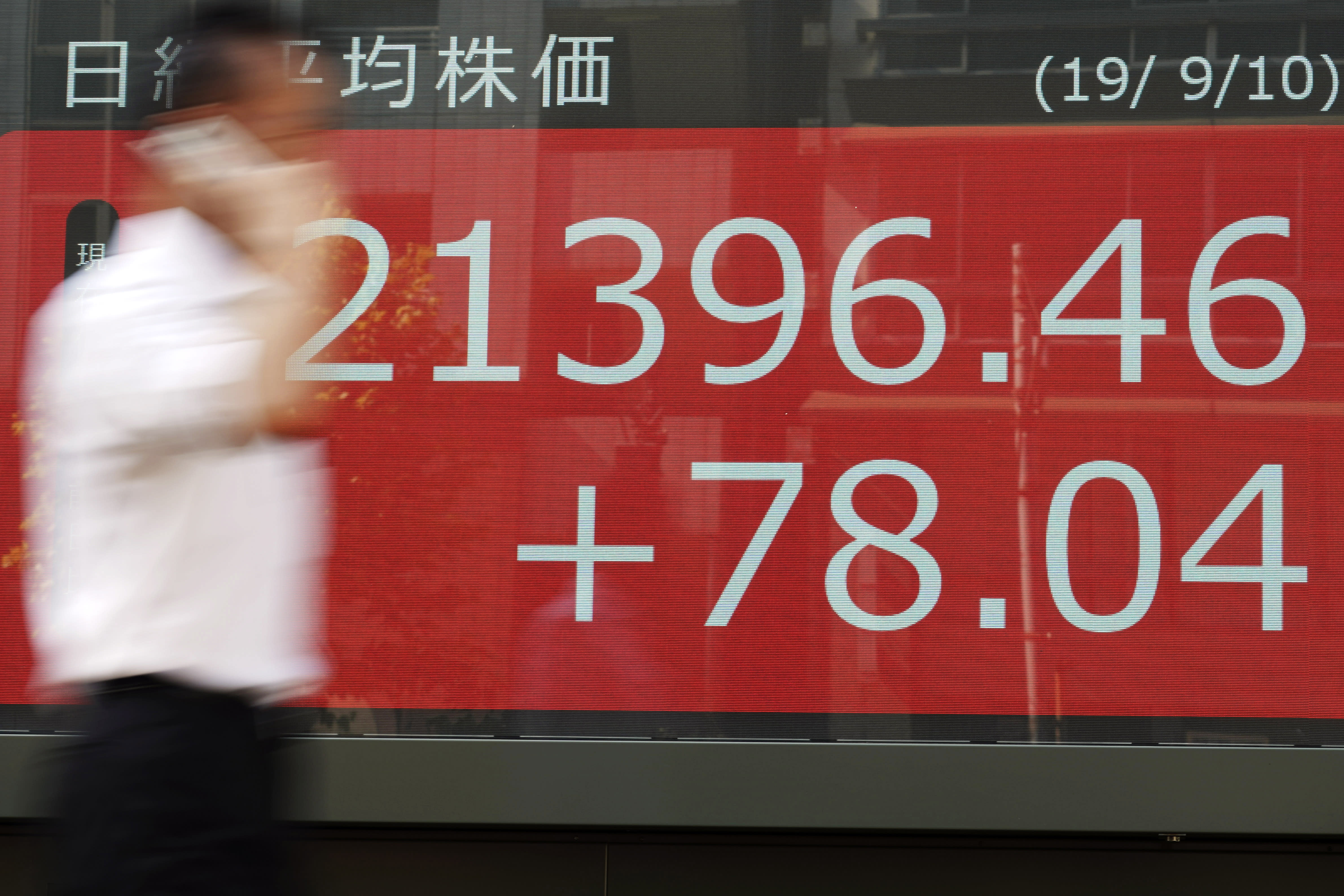 A man walks past an electronic stock board showing Japan's Nikkei 225 index at a securities firm in Tokyo Tuesday, Sept. 10, 2019. Asian shares were mixed Tuesday after a day of listless trading on Wall Street, as investors awaited signs on global interest rates. (AP Photo/Eugene Hoshiko)