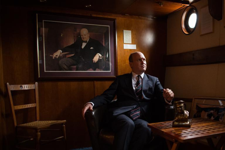 Randolph Churchill, great-grandson of late British former PM Winston Churchill, sits under a portrait of his great-grandfather, aboard the Havengore boat in central London, on January 29, 2015 (AFP Photo/Leon Neal)