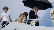 You can't stand under my umbrella! Donald Trump keeps his brolly to himself as Melania gets soaked