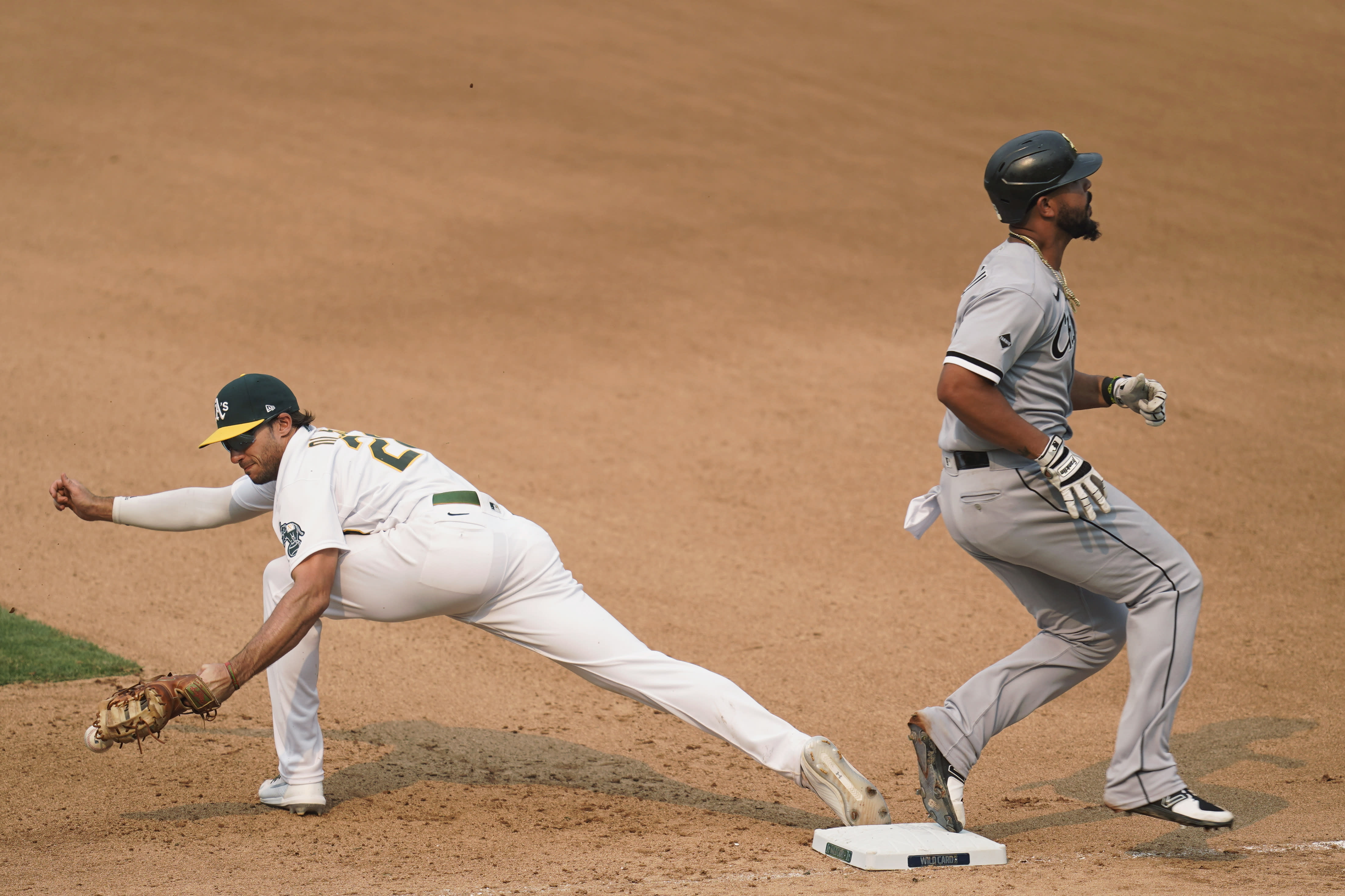 Chicago White Sox's Jose Abreu, right, reaches first as Oakland Athletics first baseman Matt Olson drops the ball on a throwing error by shortstop Marcus Semien during the seventh inning of Game 3 of an American League wild-card baseball series Thursday, Oct. 1, 2020, in Oakland, Calif. (AP Photo/Eric Risberg)