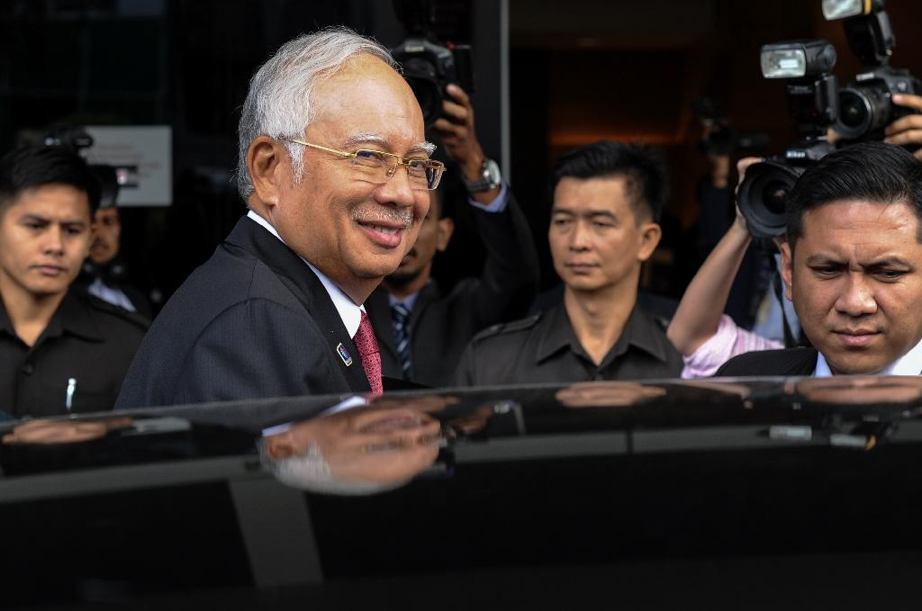 Malaysian Prime Minister Najib Razak (front) smiles to photographers after attending a parliament session in Kuala Lumpur, on January 26, 2016 (AFP Photo/Mohd Rasfan)