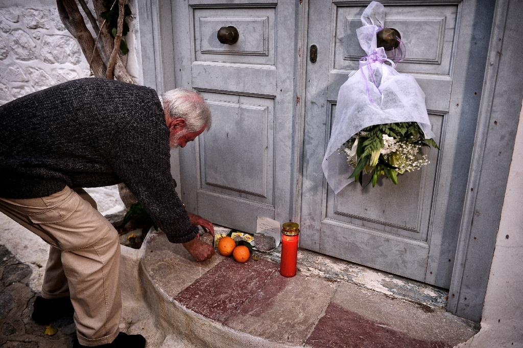 British writer and resident Roger Green leaves a stone outside the summer house of late Canadian singer-songwritter and poet Leonard Cohen, on the Greek island of Hydra, on November 11, 2016 (AFP Photo/Louisa Gouliamaki)
