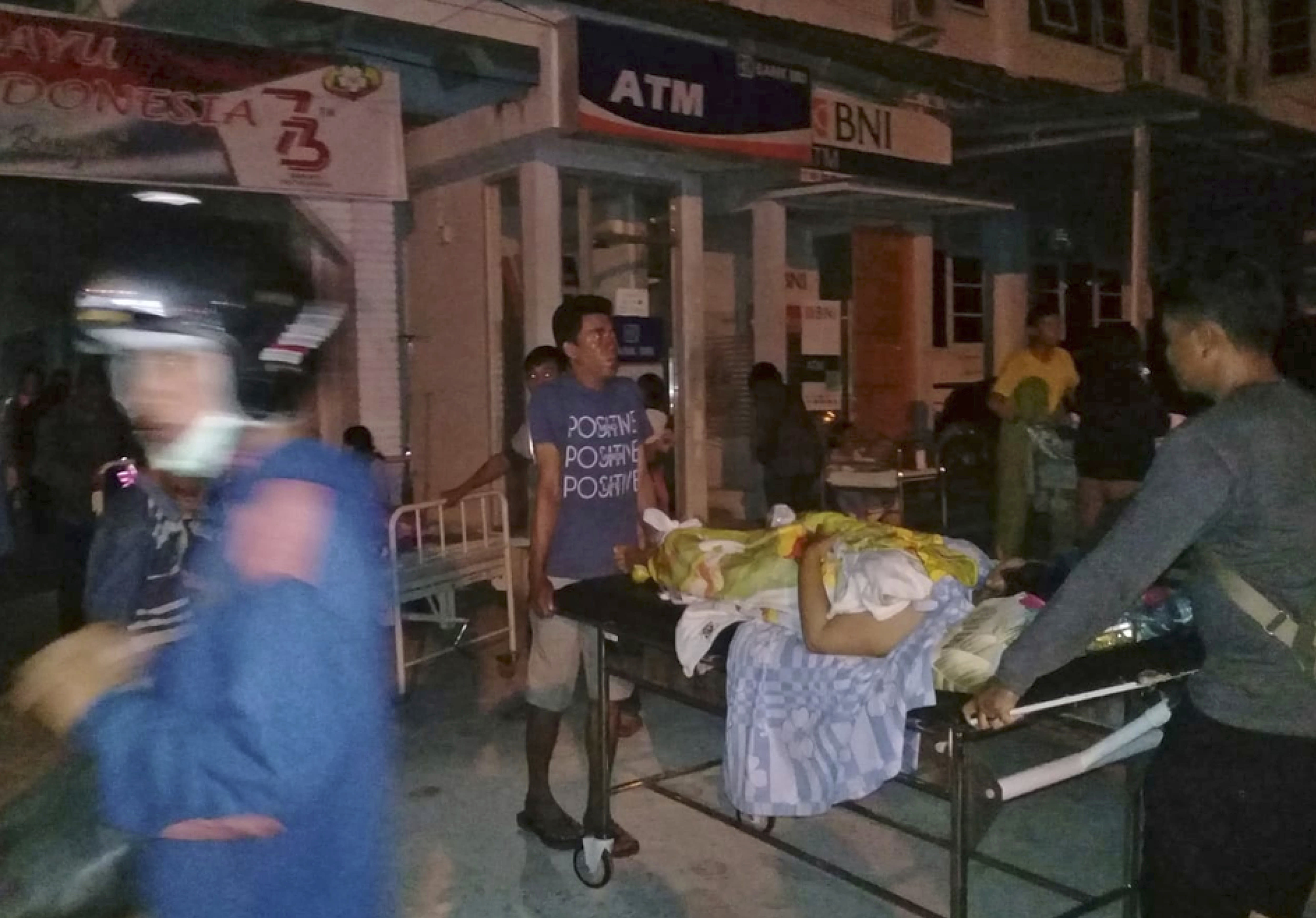 A patient is evacuated from a hospital following a strong earthquake in Poso, central Sulawesi, Indonesia, Friday, Sept. 28, 2018. Powerful earthquakes jolted the Indonesian island of Sulawesi on Friday, damaging houses and briefly triggered a tsunami warning. (AP Photo/Yoanes Litha)