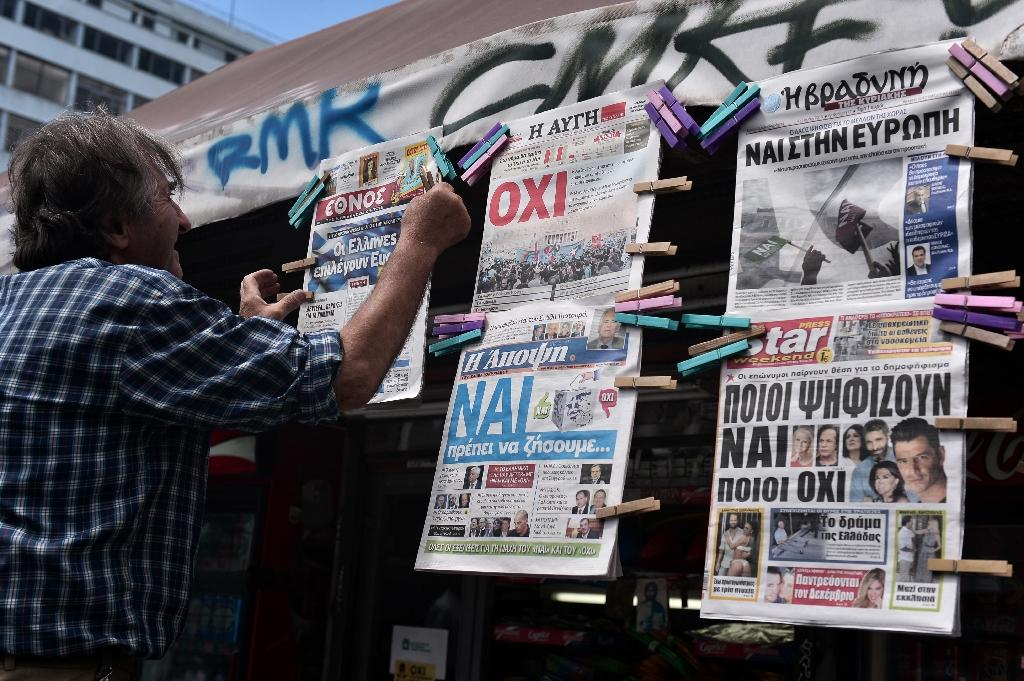 "A man hangs newspapers bearing ""No"" and ""Yes"" headlines in central Athens, on July 4, 2015, on the eve of the Greek referendum on its bailout terms (AFP Photo/Louisa Gouliamaki)"