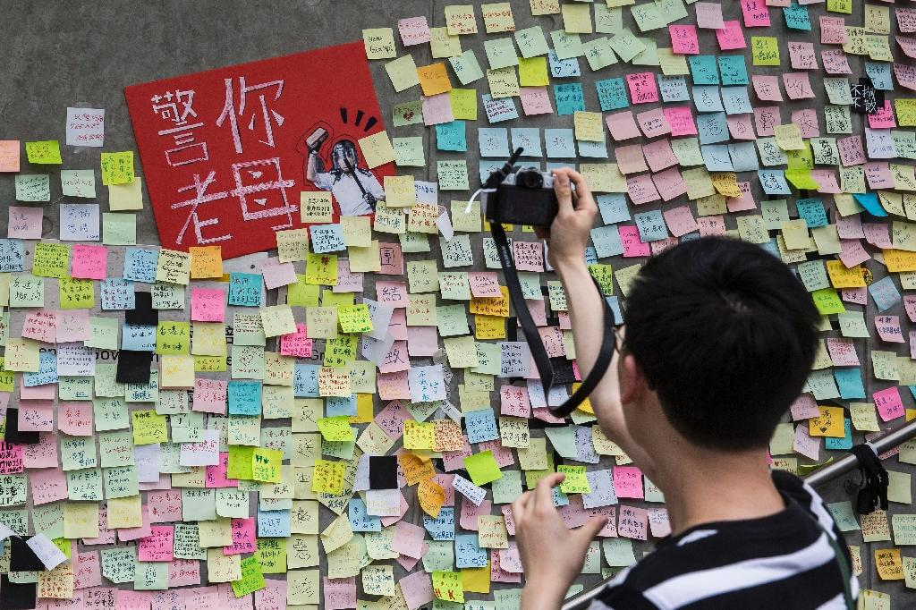 """Artwork and messages in support of protesters are posted on the """"Lennon Wall"""" outside Hong Kong's government headquarters (AFP Photo/ISAAC LAWRENCE)"""