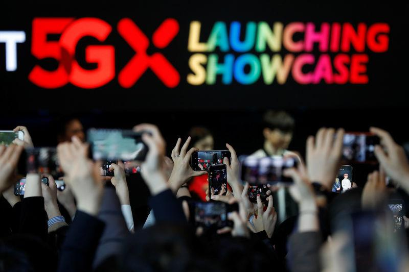 People take photographs during a launching ceremony for SK Telecom's 5G service, in Seoul