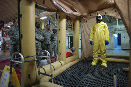 A soldier goes through the decontamination process with U.S. Army soldiers from the 101st Airborne Division (Air Assault), who are earmarked for the fight against Ebola, take part in training before their deployment to West Africa, at Fort Campbell, Kentucky October 9, 2014. REUTERS/Harrison McClary