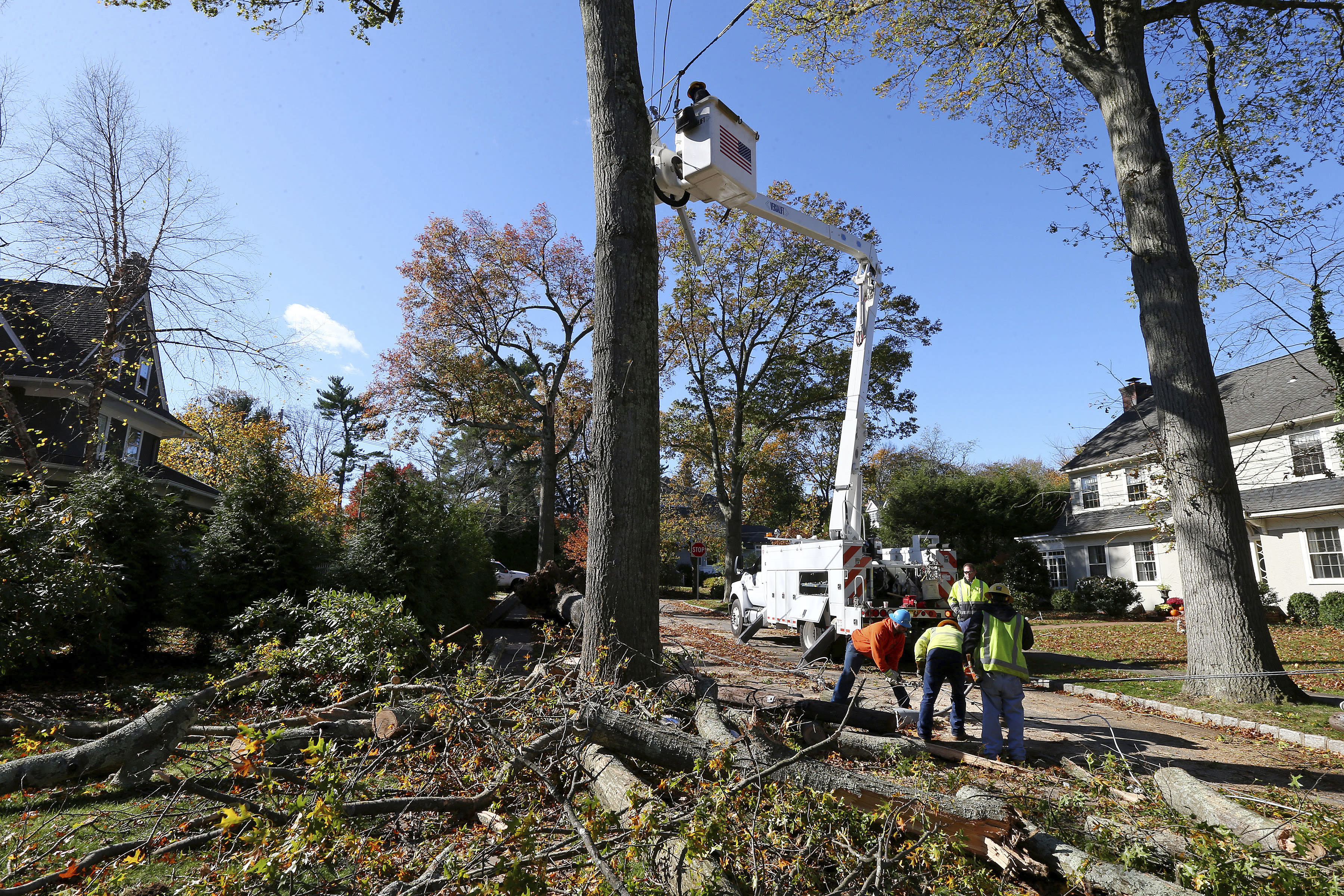 Crews from Madison Electric and Butler Municipal Power and Light work on downed power lines on Green Hill Road on Friday, Nov. 1, 2019, in Madison, N.J. The borough was hit by high winds on heavy rain late the night before. (AP Photo/Rich Schultz)