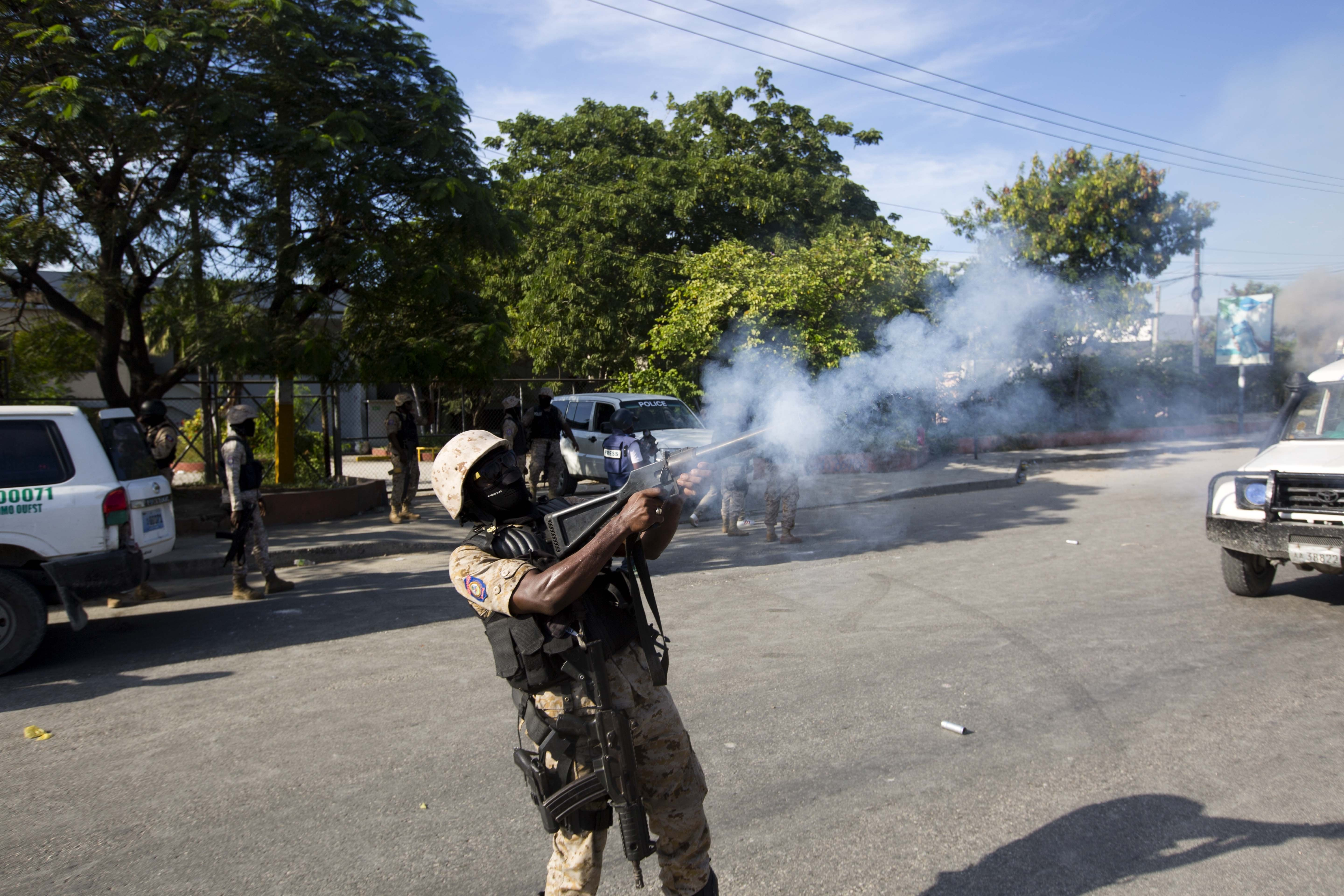 Police disperse the crowd with tear gas, away from the site where a car that careened out of control hit a group of persons in Port-au-Prince, Haiti, Wednesday, Nov. 21, 2018. According to the police the car, that was set alight by protesters, lost a wheel when it lost control and killed six persons on the street. The deaths come as Haiti faces a fourth day of protests to demand that President Jovenel Moise resign for not investigating allegations of corruption in the previous government over Petrocaribe, a Venezuelan subsidized energy program. (AP Photo/Dieu Nalio Chery)