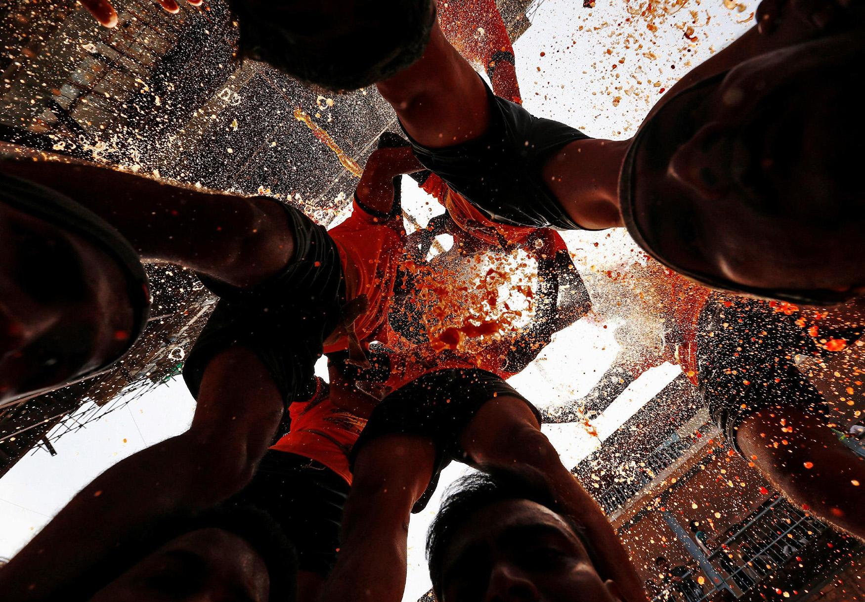 <p>A devotee breaks a clay pot containing curd as others form a human pyramid during celebrations to mark the Hindu festival of Janmashtami in Mumbai, India Aug. 25, 2016. (Photo: Danish Siddiqui/Reuters) </p>