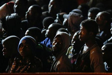 Migrants wait to disembark from a vessel in the Sicilian harbour of Augusta