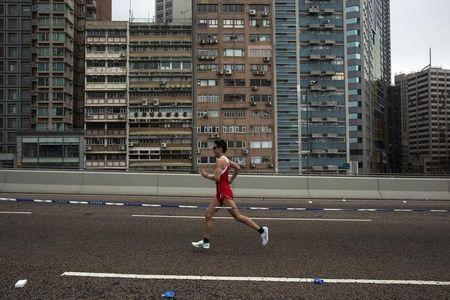 A participant runs past a old residential zone on the Connaught Road West Flyover as he competes in the Hong Kong marathon