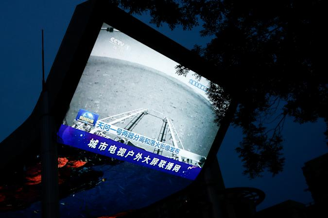 A screen broadcasts a CCTV state media news bulletin, showing an image of Mars taken by Chinese Mars rover Zhurong as part of the Tianwen-1 mission, in Beijing, China, May 19, 2021. REUTERS/Thomas Peter REFILE - CORRECTING INFORMATION