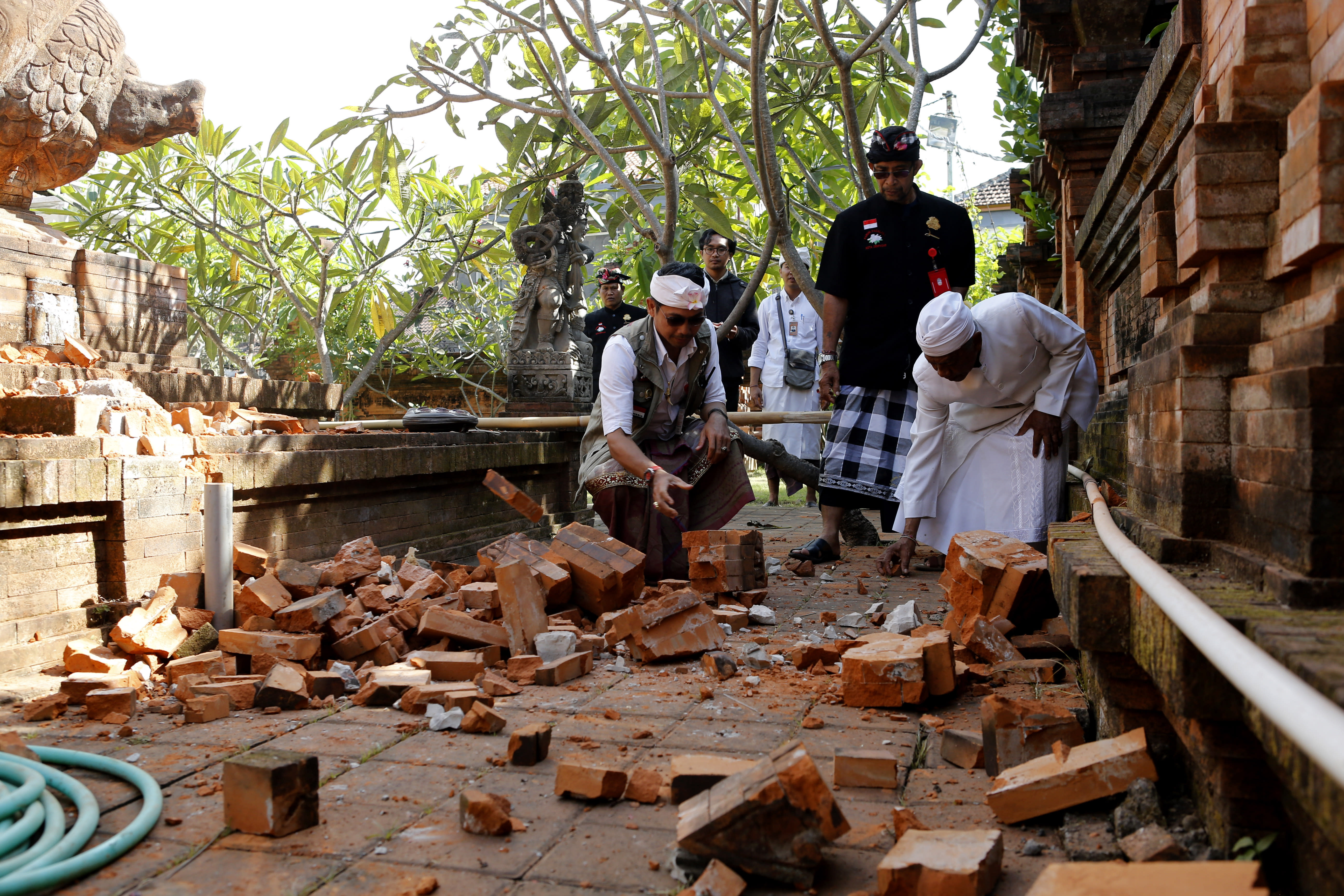 Balinese man collect stones from a damaged temple in Bali, Indonesia Tuesday, July 16, 2019. Indonesian authorities say a subsea earthquake shook Bali, Lombok and East Java on Tuesday, causing damage to homes and temples. (AP Photo/Firdia Lisnawati)
