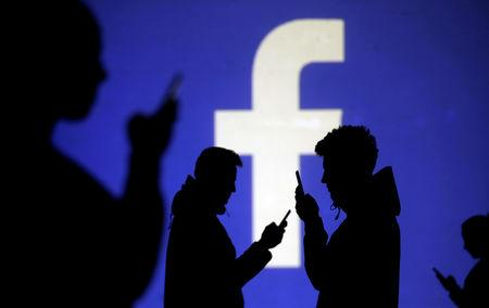Silhouettes of mobile users are seen next to a screen projection of Facebook logo in this picture illustration taken March 28, 2018. REUTERS/Dado Ruvic/Illustration/Files