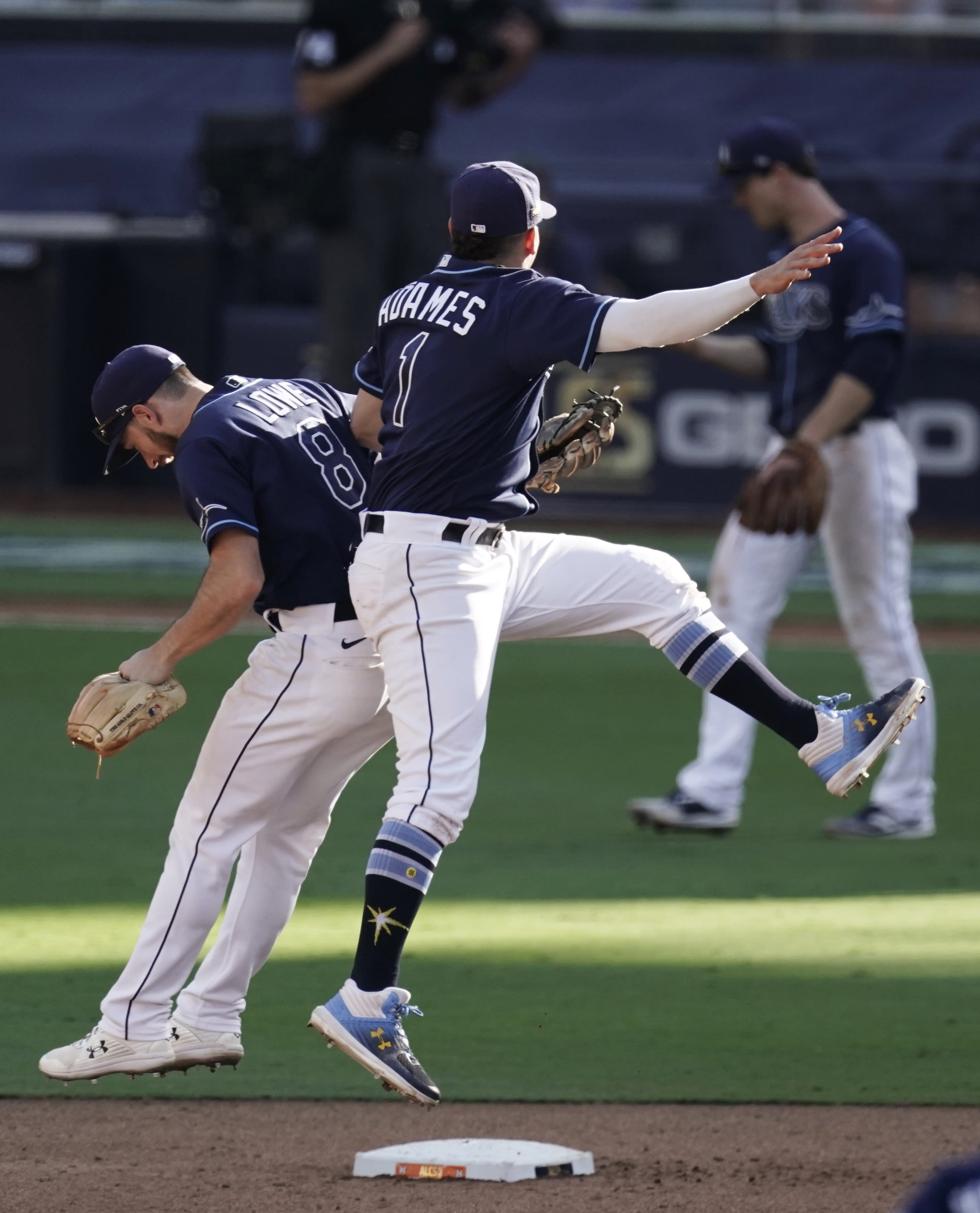 Tampa Bay Rays' Brandon Lowe (8) and Willy Adames celebrate after Game 2 of a baseball American League Championship Series, Monday, Oct. 12, 2020, in San Diego. The Rays defeated the Astros 4-2 to lead the series 2-0 games. (AP Photo/Jae C. Hong)