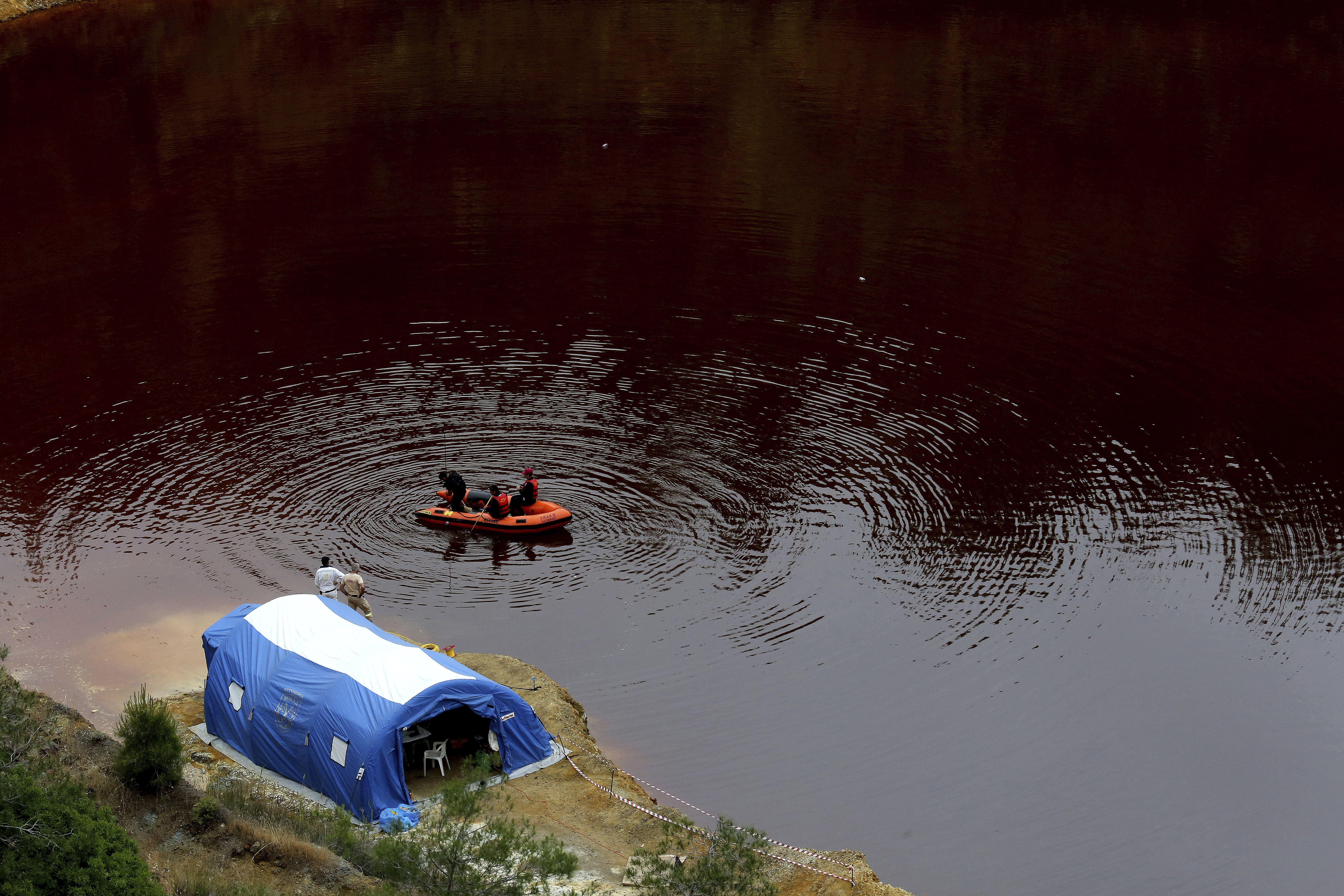 Members of the Cyprus Special Disaster Response Unit search for suitcases in a man-made lake, near the village of Mitsero outside of the capital Nicosia, Cyprus, Wednesday, May 1, 2019. Cyprus police spokesman Andreas Angelides says British experts called in to assist in the east Mediterranean island nation's serial killer case have been brought up to speed on the ongoing probe. (AP Photo/Petros Karadjias)