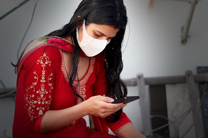 Young Indian women wearing pollution mask against Coronavirus or COVID-19 and she using mobile phone at home.