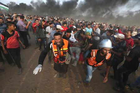 A wounded Palestinian is evacuated during a protest calling for lifting the Israeli blockade on Gaza and demanding the right to return to their homeland, at the Israel-Gaza border fence in the southern Gaza Strip October 19, 2018. REUTERS/Ibraheem Abu Mustafa