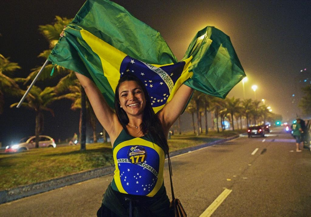 A supporter of Jair Bolsonaro celebrates outside his home in Rio de Janeiro (AFP Photo/CARL DE SOUZA)